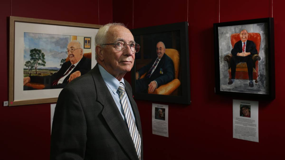 Adrian Raysmith with some of the entries in this year's Maitland Portrait Prize. Picture Simone De Peak